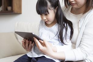 タブレットPCを見る親子の写真素材 [FYI04517060]
