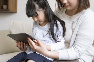 タブレットPCを見る親子の写真素材 [FYI04517061]