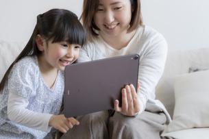 タブレットPCを見る親子の写真素材 [FYI04517074]