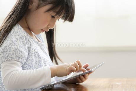 タブレットPCを見る女の子の写真素材 [FYI04517077]