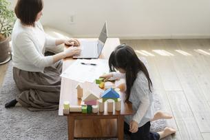 積み木で遊ぶ女の子とテレワークをする母親の写真素材 [FYI04517091]