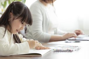 お絵描きをする女の子とテレワークをする母親の写真素材 [FYI04517097]