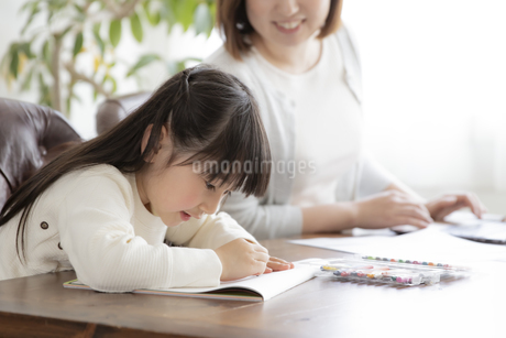 お絵描きをする女の子とテレワークをする母親の写真素材 [FYI04517099]
