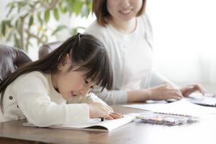 お絵描きをする女の子とテレワークをする母親の写真素材 [FYI04517100]