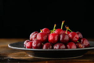 Ripe red cherries in black plate.の写真素材 [FYI04519840]