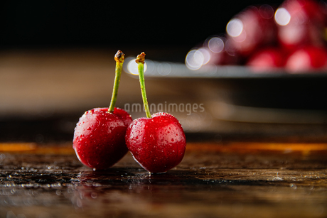 Ripe red cherries on wood table.の写真素材 [FYI04519851]