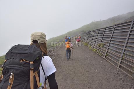 富士を霧の中登山する女性の後ろ姿の写真素材 [FYI04520625]