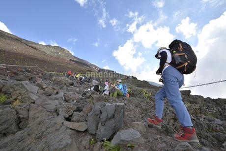 富士山の岩場を登る女性の写真素材 [FYI04520628]