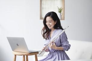 ノートパソコンを見ながらフルートを持つ女性の写真素材 [FYI04521072]