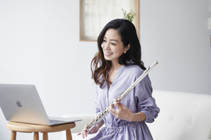 ノートパソコンを見ながらフルートを持つ女性の写真素材 [FYI04521074]