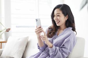 ソファに座りスマートフォンを見る女性の写真素材 [FYI04521115]