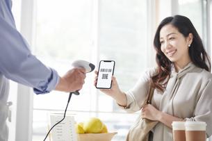 スマートフォンを持ちキャッシュレス決済をする女性の写真素材 [FYI04521141]