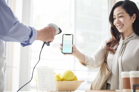 スマートフォンを持ちキャッシュレス決済をする女性の写真素材 [FYI04521144]