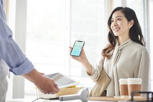 スマートフォンを持ちキャッシュレス決済をする女性の写真素材 [FYI04521148]