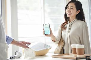 スマートフォンを持ちキャッシュレス決済をする女性の写真素材 [FYI04521152]