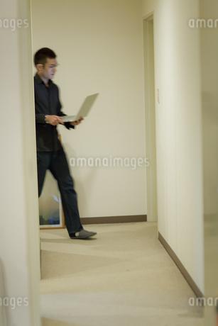 廊下を歩きながらパソコンを使う男性の写真素材 [FYI04521181]