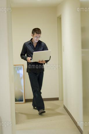 廊下を歩きながらパソコンを使う男性の写真素材 [FYI04521182]