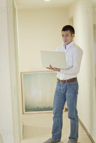 オフィスで立ちながらパソコンを使う男性の写真素材 [FYI04521187]