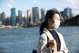 ビル群の前でマスクをしている女性の写真素材 [FYI04521246]