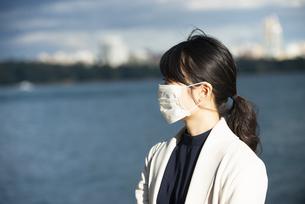 海をバックにマスクをしている女性の写真素材 [FYI04521249]