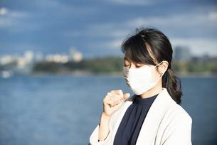 マスクをして咳をしている女性の写真素材 [FYI04521598]