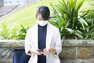 マスクをしてスマホを見ている女性の写真素材 [FYI04521609]