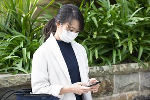 マスクをしてスマホを見ている女性の写真素材 [FYI04521611]