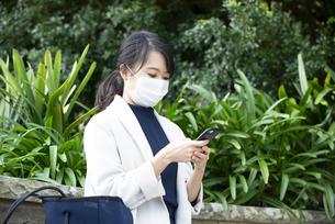 マスクをしてスマホを見ている女性の写真素材 [FYI04521613]