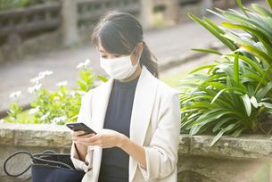 マスクをしてスマホを見ている女性の写真素材 [FYI04521619]