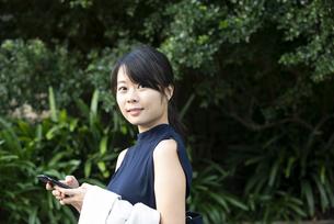 スマホを持ってこちらを見ている女性の写真素材 [FYI04521659]