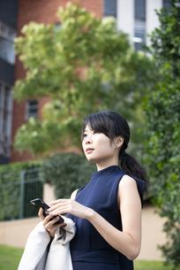 スマホを持って遠くを見ている女性の写真素材 [FYI04521688]