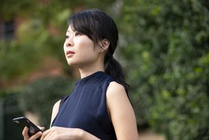 スマホを持って遠くを見ている女性の写真素材 [FYI04521690]
