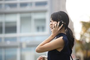 ビルの前で電話をしている女性の写真素材 [FYI04521718]