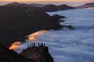 槍の肩から西鎌尾根を見下ろす。夕日に照らされた雲海と見物する登山客。の写真素材 [FYI04524590]