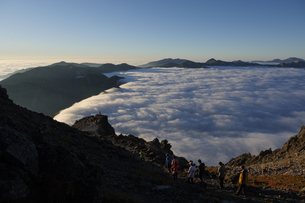 槍の肩から西鎌尾根を見下ろす。夕日に照らされた雲海と見物する登山客。の写真素材 [FYI04524592]