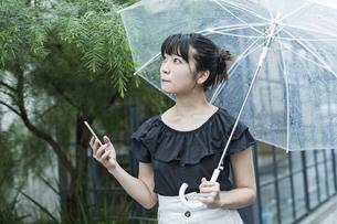 女性 雨 散歩 スマホの写真素材 [FYI04524666]