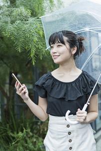 女性 雨 散歩 スマホの写真素材 [FYI04524667]