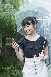 女性 雨 散歩 スマホの写真素材 [FYI04524668]