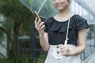 女性 雨 散歩 スマホの写真素材 [FYI04524669]