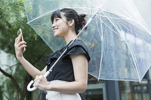 女性 雨 散歩 スマホの写真素材 [FYI04524672]