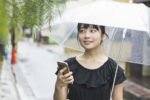 女性 雨 散歩 の写真素材 [FYI04524779]