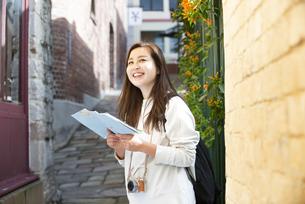 街で地図を持って笑っている女性の写真素材 [FYI04525608]