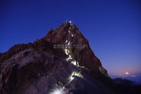 槍の肩から見る槍ヶ岳に登る登山客のヘッドライトの列。の写真素材 [FYI04525734]