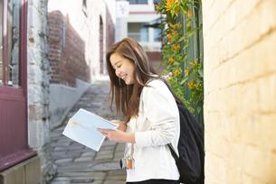 街で地図を見ながら笑っている女性の写真素材 [FYI04526826]