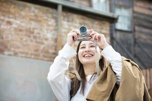 街でカメラを構えて笑っている女性の写真素材 [FYI04526839]