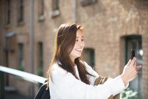 街中で自撮りをしている女性の写真素材 [FYI04526863]