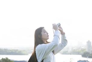 カメラで空を撮影している女性の写真素材 [FYI04526878]