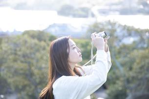 カメラで空を撮影している女性の写真素材 [FYI04526879]
