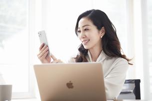 スマートフォンを持ち会話する女性とノートパソコンの写真素材 [FYI04527186]