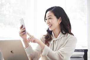 スマートフォンを持ち会話する女性とノートパソコンの写真素材 [FYI04527187]